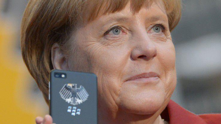 Angela Merkel mit einem Smartphone auf der CeBIT 2013
