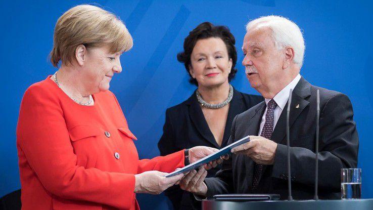 Der Vorsitzende des Normenkontrollrats Johannes Ludewig überguibt Bundeskanzlerin Angela Merkel den Jahresbericht 2017: Bürokratieabbau. Bessere Rechtssetzung. Digitalisierung Sein Fazit: E-Government gibt es in Deutschland de facto nicht.