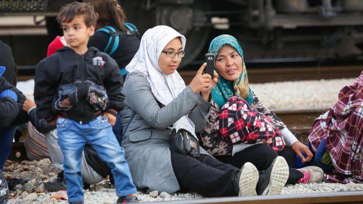Das Smartphone ist für viele Flüchtlinge der einzige Weg, um Kontakt zu Freunden und Familie in der Heimat zu halten. Die Mobilfunkbranche reagiert auf den wachsenden Bedarf.