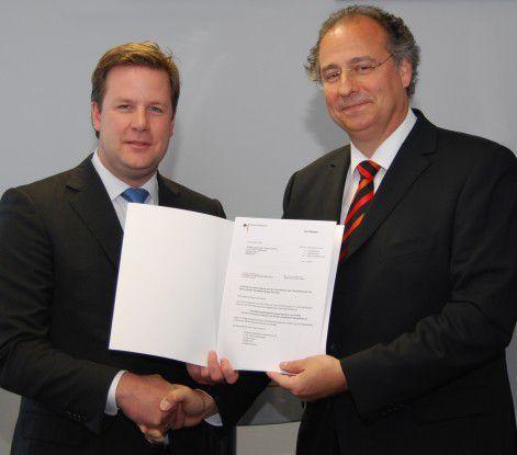 Christoph Verenkotte (rechts) übergibt das erste Berechtigungszertifikat an Oliver Schoeller, Mitglied des Vorstands der Gothaer Versicherungen.